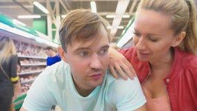 Dans le supermarché, un plan rapproché du visage du mari qui attend son épouse tandis qu'elle fait des emplettes au magasin alésé banque de vidéos