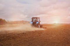 Dans le tôt, matin de ressort, en raison du bois le soleil lumineux monte Le tracteur disparaît et tire une charrue Photographie stock libre de droits