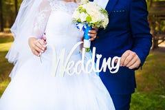 Dans les mains des nouveaux mariés épousant les lettres en bois Photo libre de droits