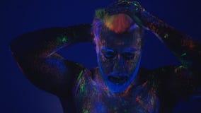 Dans in ultraviolet licht Een onwerkelijke dans van een mens in het ultraviolette licht De sterke, spiermens is een afbijtmiddel stock footage