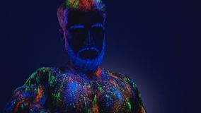 Dans in ultraviolet licht Een onwerkelijke dans van een mens in het ultraviolette licht De sterke, spiermens is een afbijtmiddel stock videobeelden