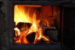 Dans un bois de chauffage brûlant de bouleau de four Photo stock