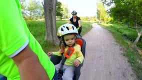 Dans un fauteuil du ` s d'enfants, un enfant monte une bicyclette Mouvement lent banque de vidéos