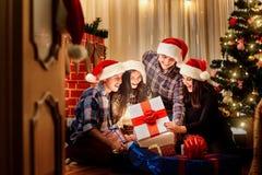 Dans un groupe d'amis dans des chapeaux de Noël sur le plancher dans la chambre Photos libres de droits