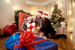 Dans un groupe d'amis dans des chapeaux de Noël sur le plancher dans la chambre Photos stock