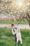 Dans un jardin luxuriant et un garçon de chèvre Photo stock