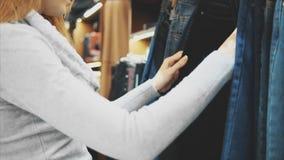 Dans un magasin moderne, la fille regarde les modèles du pantalon banque de vidéos