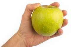 Dans une main une pomme verte d'isolement sur un fond blanc Photo stock