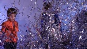Dansa barn som upp kastar glitter p? gr? bakgrund, ultrarapid arkivfilmer