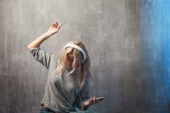 Dansa den attraktiva kvinnan som lyssnar till musik i mobilen app Flickamusikvän royaltyfria bilder