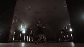 Dansa en l?ngsamt ballerina av fl?cken t?nder framme Flera strålkastare visar en dansa ballerina på en mörk etapp i långsamt stock video