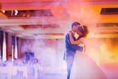 Dansa först bruden och brudgummen i röken Arkivfoton