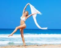 Dansa lycklig flicka på stranden Arkivbild