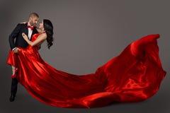 Dansa par, kvinnan i röd klänning och mannen i dräkten, vinkande tyg arkivfoton