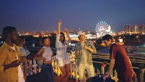 Dansar den blandras- gruppen för vänner på tak på natten som har det frilufts- partiet, medan discjockeyn arbetar med utrustning  arkivfilmer