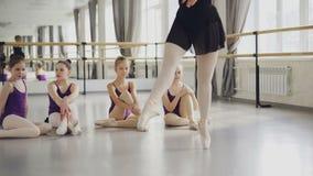 Dansar den yrkesmässiga ballerina för balettläraren på tåspetsarna som visar förehavanden till hennes lilla studenter som är lager videofilmer