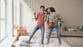 Dansar unga roliga flickor för blandat lopp att sjunga med hårtork och att spela den akustiska gitarren på en säng gyckel som har