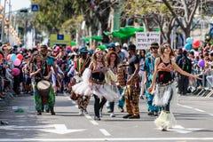 Dansare i mång--färgade klänningar deltar i den årliga karnevalet av Adloyada klädde, som spanar går med valsar i Nahariyya, är Arkivbilder