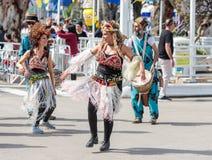 Dansare i mång--färgade klänningar deltar i den årliga karnevalet av Adloyada klädde, som spanar går med valsar i Nahariyya, är Royaltyfria Bilder