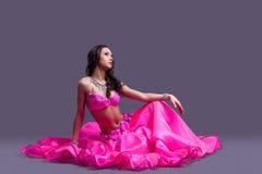 Dansare i orientaliska rosa färg kostymerar sammanträde däckar på Royaltyfri Bild