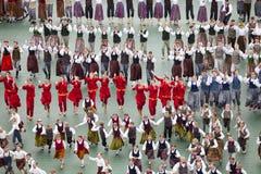 Dansare i traditionella dräkter utför på den storslagna folkdanskonserten av den lettiska ungdomsången och dansar festival Royaltyfria Bilder