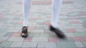 Dansare` s lägger benen på ryggen närbilden, ögla Flicka som solo dansar jazzgungadans Rolig dans på trottoaren för fyrkant för s stock video