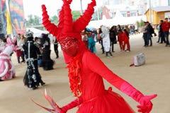 Dansaren i röd dräkt poserar på gatateatrar visar på nätter för festivalen för öppen luft vita Royaltyfri Bild