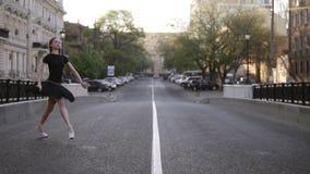 Dansballerina i praktiserande rätt för svart balettballerinakjol och för svart T-skjorta på gatan Konstruktion av en bro över fjä stock video