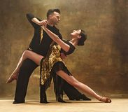 Dansbalsalpar i guld- klänningdans på studiobakgrund royaltyfria foton