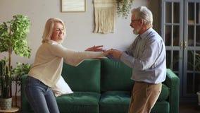 Danse âgée active heureuse de couples ayant l'amusement à la maison ensemble banque de vidéos