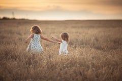 Danse émotive de deux filles de soeurs au coucher du soleil image stock