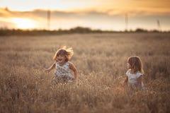 Danse émotive de deux filles de soeurs au coucher du soleil image libre de droits