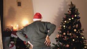 Danse barbue heureuse d'homme près de l'arbre de Noël L'homme bel heureux dans le chapeau de Santa déplace son corps de manière d banque de vidéos