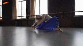Danse blonde de fille dans le studio pr?s des fen?tres dans la jupe bleue - contemporain banque de vidéos