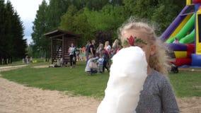 Danse charismatique de fille au parc d'attractions l'enfant 4 années mange la sucrerie de coton banque de vidéos