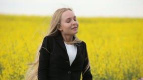 Danse d'adolescente dans le domaine jaune de floraison banque de vidéos