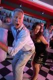 Danse d'homme aîné avec un plus jeune femme dans le bar occupé Photographie stock libre de droits