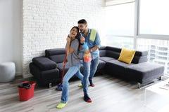 Danse d'homme et de femme tout en nettoyant à la maison image stock