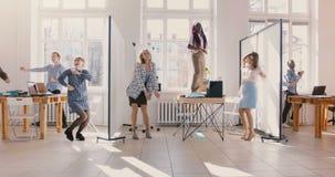 Danse d'hommes d'affaires d'amusement dans le bureau moderne léger, équipe saine multi-ethnique de lieu de travail célébrant  banque de vidéos