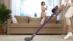 Danse de femme au foyer avec un aspirateur dans le salon Sa petite fille sautant sur le divan Mouvement lent clips vidéos