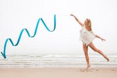 Danse de femme de gymnaste avec le ruban sur la plage Image libre de droits