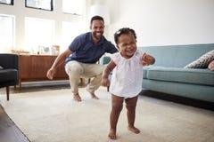Danse de fille de bébé avec la maison d'In Lounge At de père image stock