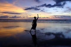 Danse de fille dans le coucher du soleil sur la plage Image stock
