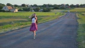 Danse de fille de brune sur une route banque de vidéos