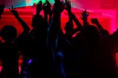 Danse de gens dans le club avec le lightshow Photographie stock