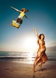 Danse de mère et de descendant sur la belle plage. Photographie stock