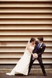 Danse de marié et de jeune mariée près d'un mur dépouillé Photo libre de droits