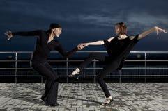 Danse de salon supérieure de couples sur le coucher du soleil foncé Photographie stock libre de droits