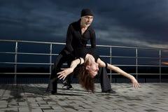 Danse de salon supérieure de couples sur le coucher du soleil foncé Photo stock