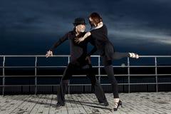 Danse de salon supérieure de couples sur le coucher du soleil foncé Photographie stock
